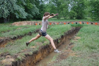 She's jumping over the ditch.